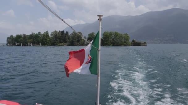 Italien-Flagge mit Wappen weht im Wind eines Bootes, das Brissago verlässt.