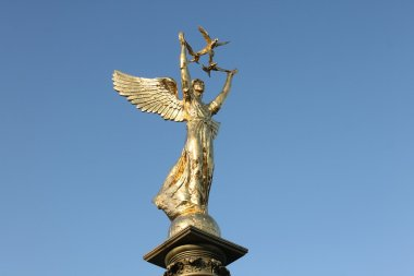 The Golden statue of the goddess Nike at blue sky background