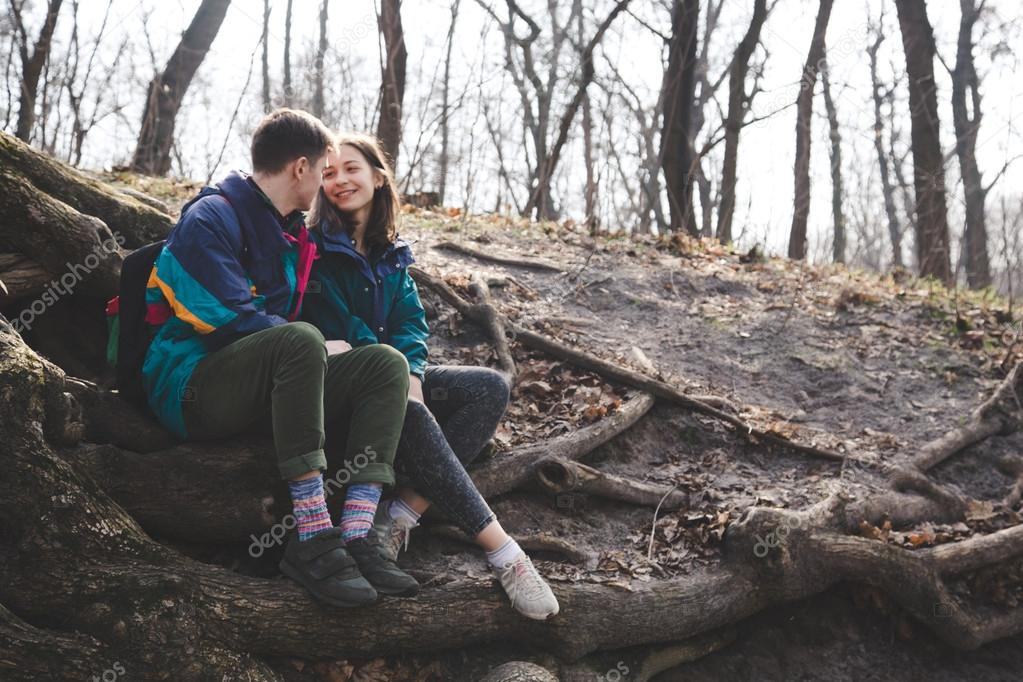 Young beautiful happy hipster couple brunette girl and guy having great fun time while travelling and walking in the woods forest