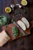 italienische Pesto-Zubereitung vegane Version ohne Parmesan mit schwarzen Oliven statt alle Zutaten auf Tisch grünem Basilikum, Knoblauch, Zitrone, Pinienkernen, schwarzen Oliven alle frisch und bio auf dunklem Holz rustikalem Tischhintergrund