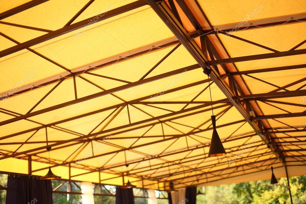 Gele achtergrond met moderne plafondlamp in het café en interieur