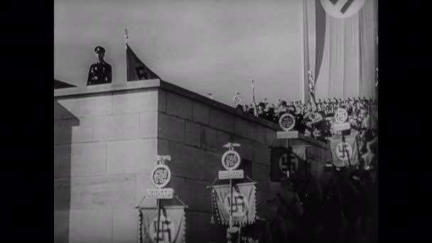 1940s EUROPE: Nazis march at rally. Hitler stands on dais. Band plays. Crowd gives Nazi salute.