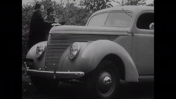 30. léta: Auto zaparkované na kraji silnice. Dvě ženy se dívají na auto. Auto se zapne na jevišti.