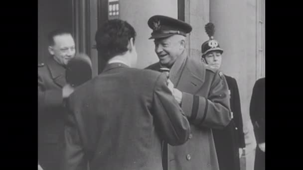 1950s Europe: Man pastes poster to wall. General Eisenhower speaks to men. Cars drive through police and crowds in streets of Paris. Military officers meet and talk in building.