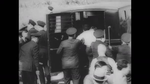 Třicátá léta Chicaga: Muž nasedne do policejního auta a drží si hlavu. Fotograf fotí.