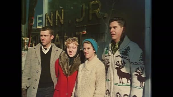 1960s: Four young people watch parade. Slate w/ Title Inaugural Ceremony, Proj. No I-65/144, Name Rushton. Two sailors wear Dixie Cup hat and watch parade. Flags and seal decorations on lamppost.