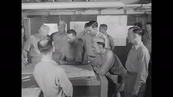 1940s: Military personnel gathered around maps on table, man exits. Men looking at chart, man points to chart.