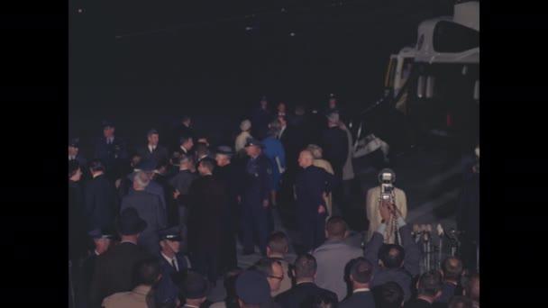 Washington DC: Muži vedou prezidenta Johnsona a jeho ženu do helikoptéry. Muž v obleku sestupuje po schodech z Air Force One na přistávací dráhu.