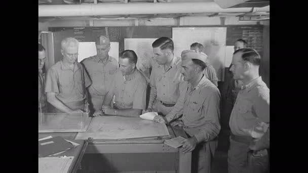 1940s: Military personnel gathered around maps on table, man exits. Men looking at chart, men turn, gather around table.