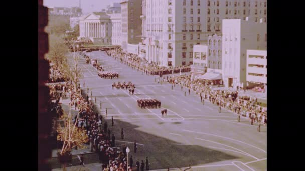 1960s Washington DC: Soldiers march before Kennedy funeral procession on streets of Washington DC. Crowds and soldiers stand on roadside and view funeral procession.