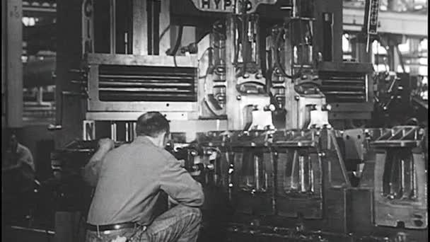 1940er Jahre: Mann steuert Maschine in Fabrik.