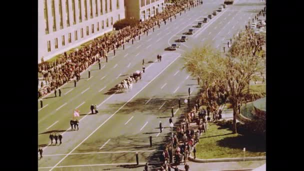 1960s: Horses pull carriage with casket down road in funeral procession for John F. Kennedy.
