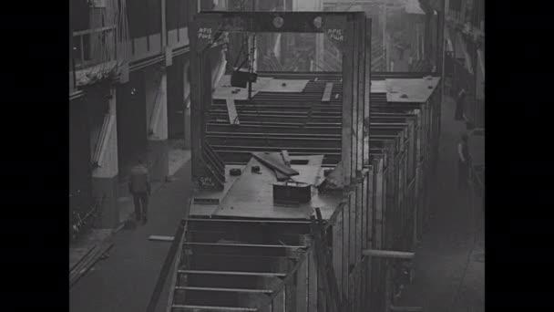 1910er Jahre: Männer arbeiten an der Struktur eines Militärbootes in einem großen Industrielager. Kran hebt Blech auf Bootsbaustelle.