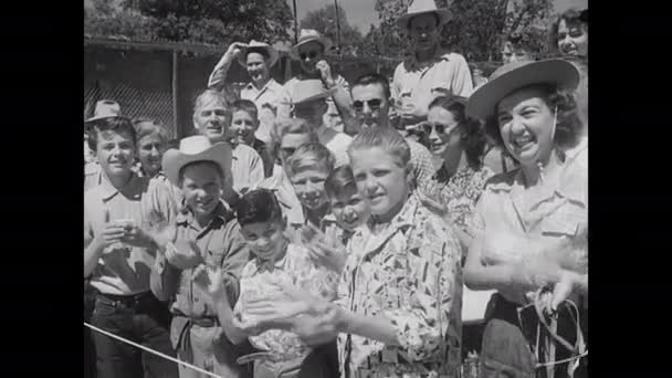 1960er Jahre: Der Mensch platziert den Frosch im Kreis, der Frosch springt, der Mensch markiert Sprünge, die Menge klatscht. Frau im Diadem hält Frosch. Die Leute spielen Baseball, die Fans schauen von der Tribüne zu. Umpire staubt Teller ab.