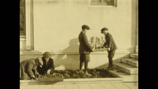 1920er Jahre: Zwei Jungen pflanzen Pflanzen im Garten außerhalb des Gebäudes. Kinder bearbeiten Gärten in der ganzen Landschaft vor dem Gebäude. Mann im Anzug weist Arbeiter an Feld zu pflügen.