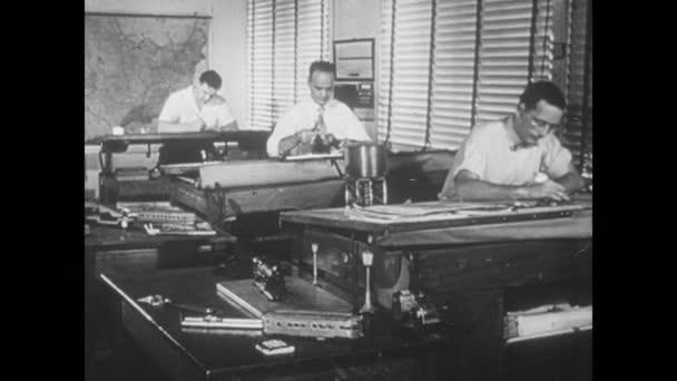 1950er Jahre: Führungskräfte diskutieren Prototypen von Modelleisenbahnen. Designer an Zeichentischen studieren Modellbahnwagen und Fotografien. Designer zeichnen und verwenden Lineale. Echte Lokomotiven rasen über die Gleise.