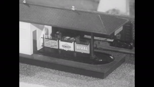 1950er Jahre: Geladener Gepäckwagen kreist in den Bahnhof. Gepäckwagen verlässt Bahnhof entladen. Modellbahnwagen mit Aussichtsplattform. Modelleisenbahnen bewegen sich auf Gleis.