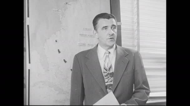 1950s: Man stands at map explaining likely trajectory of hurricane landfall.