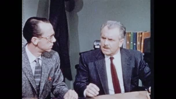 1950er Jahre: Zwei Männer sitzen am Schreibtisch, reden, schauen schockiert und aufgebracht.