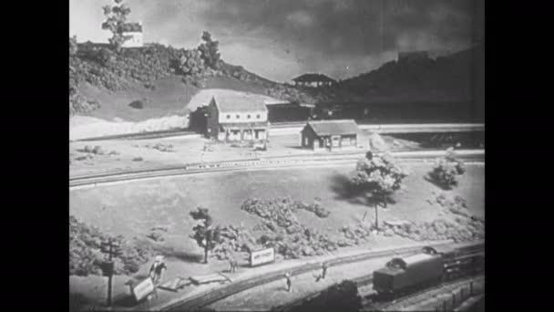 1950er Jahre: Modelleisenbahnen fahren auf Gleisen durch Anlagen. Rauch quillt aus Lokomotivstapel.