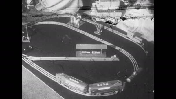 1950er Jahre: Spielzeugeisenbahnen kreisen weiter über die Gleise. Vater lächelt und blickt in die Ferne, erinnert sich. Spielzeugeisenbahnen säumen die Regale.