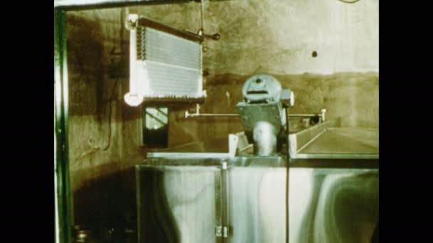 1950: Velké nerezové nádoby. Muž zvedá víko kontejneru, nakukuje dovnitř, mluví a ukazuje.