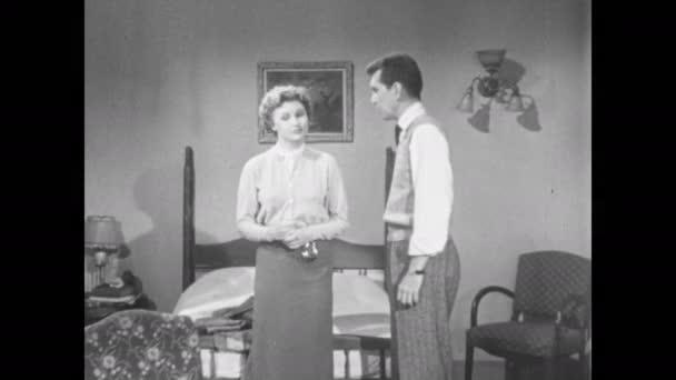 1950: Muž a žena si povídají v hotelovém pokoji, žena zvedne bundu a položí ji na postel. Žena mluví a sedí na židli.