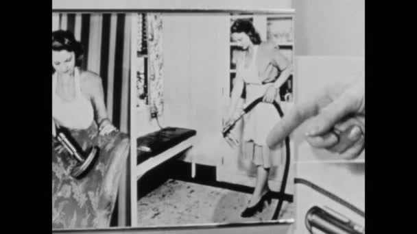 1940s: Domácí spotřebiče showroom, prodavač ukazuje na fotografii ženy pomocí vakuového postřikovače připojení, gesta, spočívá na ruce na vakuu, mluví sebevědomě. Žena poslouchá, drží rukavice.