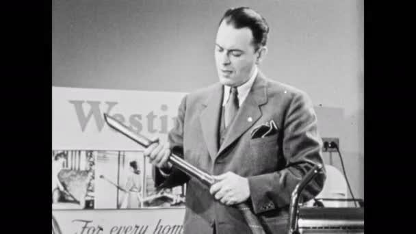 1940s: Domácí spotřebiče showroom, prodavač stojí před Westinghouse vakuové displeje, demonstruje příloh, přikyvuje, vypadá sebejistě, ukazuje na fotky žen úklidové židle, žaluzie.