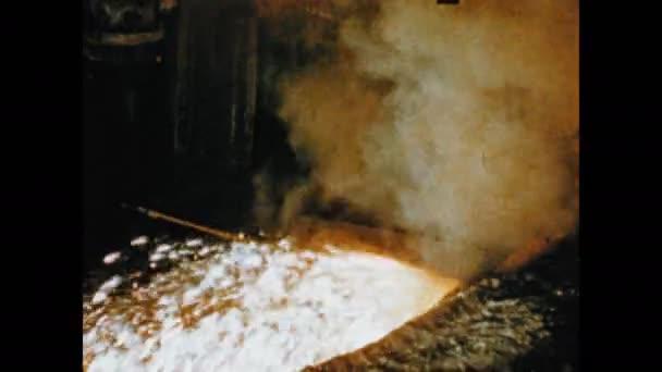 1950s: Conveyor belt.  People in furnace works.  Flames.  Sparks.  Explosion.  Ore flows into pit.  Man speaks.