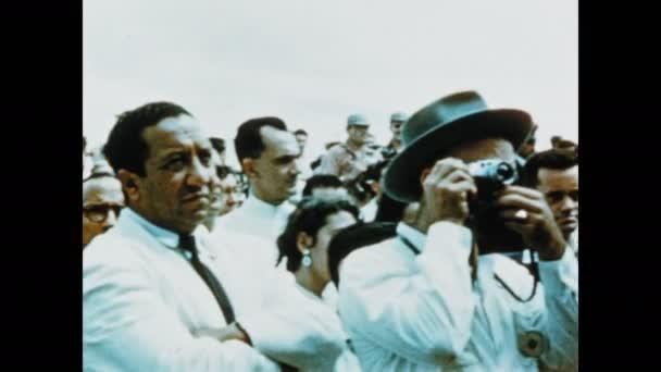 1950s: Crowd.  Men with cameras.  Man makes speech.