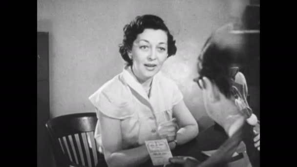 1940er Jahre: Frau sitzt hinter einem Schreibtisch, spricht mit Menschen, reicht Menschen Papiere, Menschen unterschreiben Papiere.