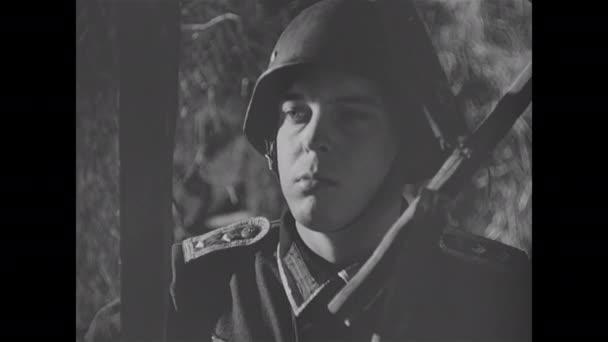 1940: Voják v helmě stojí venku a natahuje polní telefon. Armádní důstojník ukazuje na mapu na zdi a kruhy na mapě.