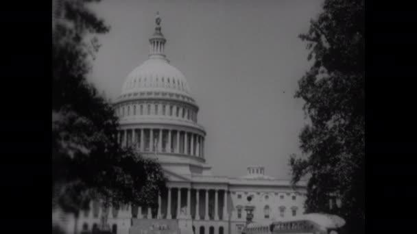 50. léta: budova hlavního města USA. Vstup do Národní tiskové budovy. Dva muži se dívají na papíry na stole. Tisk, noviny. Ten chlap dává balík novin do náklaďáku. Lidé kupují noviny.