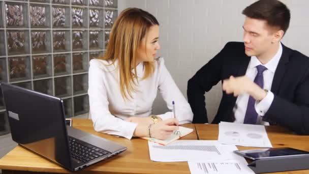 Podnikatelé mají schůzku u stolu v moderní kanceláři