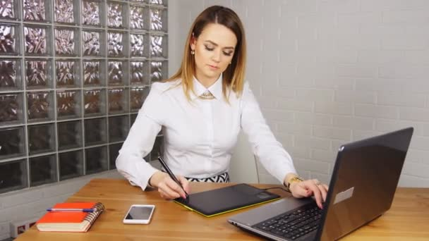 Young woman working in office with graphic tablet