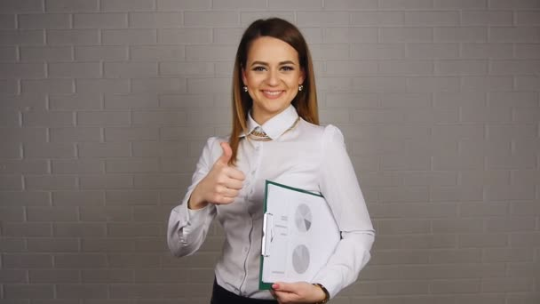Businesswoman holding documents and showing thumb up