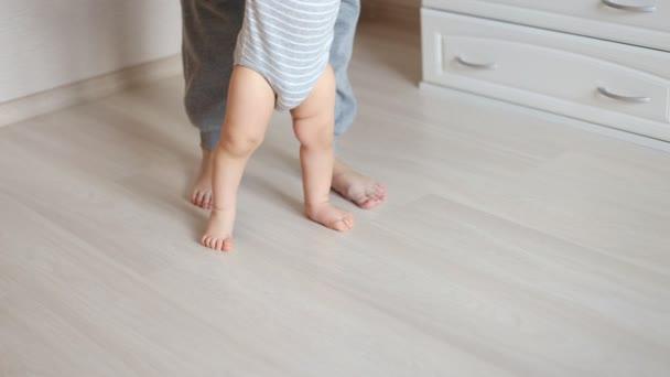 Mutter und Baby Beine. Erste Schritte.