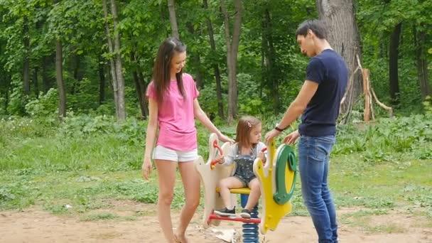 Hravé dítě s rodiči na venkovním hřišti. Máma, táta a dítě