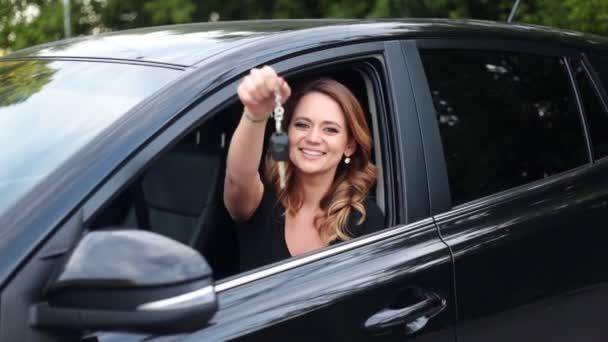 Autofahrerin mit Autoschlüssel am Steuer ihres neuen Autos.