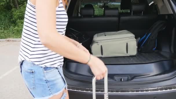 Beautiful girl in a car trunk loads