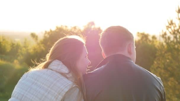 Rückansicht eines jungen glücklichen Paares bei Sonnenuntergang