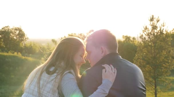 back view of young happy couple sitting at sunset
