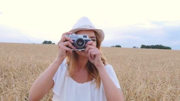 Donna che cattura foto con fotocamera a pellicola retrò sul campo