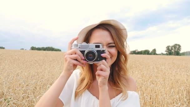 Frau fotografiert mit Retro-Filmkamera auf dem Feld