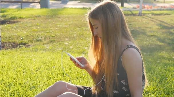 Fiatal nő a fű, telefon