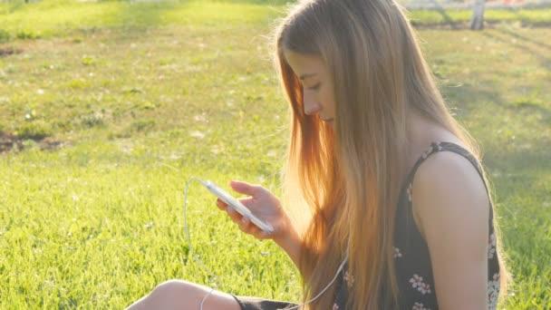 Mladá žena na trávě s telefonem