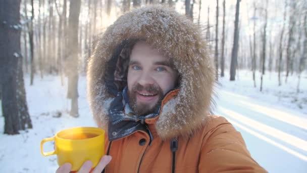 Téli turizmus és túrázás koncepció. Fiatal szakállas férfi szelfit készít az erdőben egy bögre forró teával a téli erdőben.