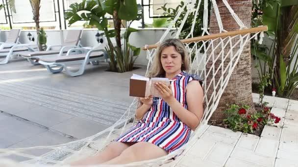 Lady, čtení knihy v houpací síti u bazénu