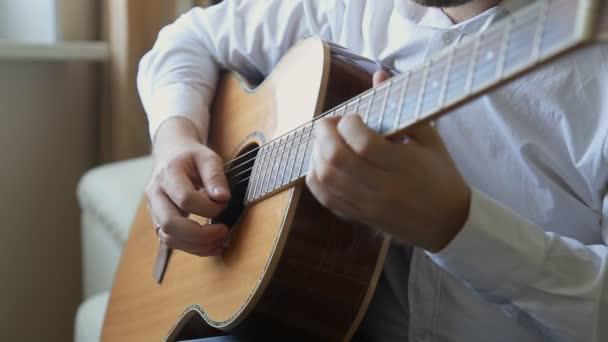 kytarista hraje na akustickou kytaru doma